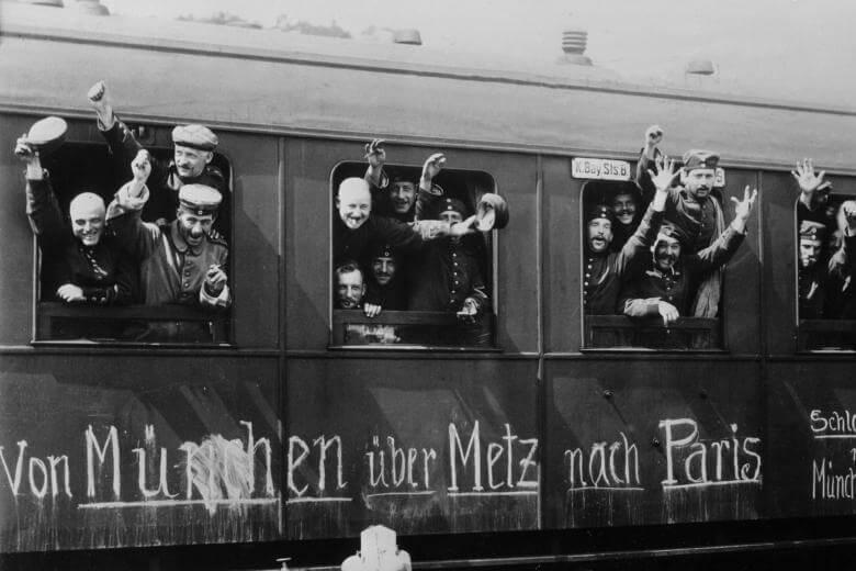Bayerische Soldaten winken in euphorischem Glauben an einen schnellen Sieg aus den Fenstern eines Zuges
